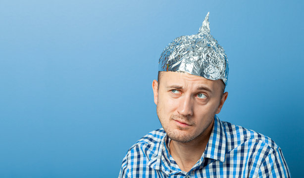 Foil hat on man. Man with a surprised face. Protects from reading think