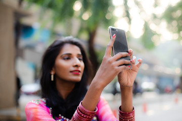 Young Indian Woman Taking photos with smartphone outdoor