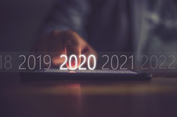 Business men press numbers 2020 at the mobile phone screen .Concept welcome merry christmas and happy new year 2020