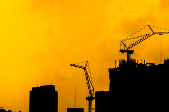 Silhouette crane and construction building site,Building crane and buildings under construction.