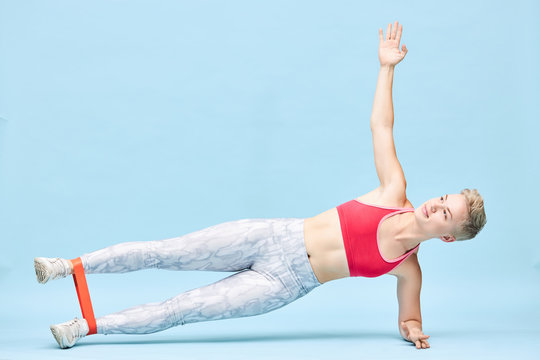 Horizontal shot of beautiful energetic sporty girl performing side plank on floor in gym with resistance band around her ankles doing side lifts, strengthening hip abductor muscles, smiling