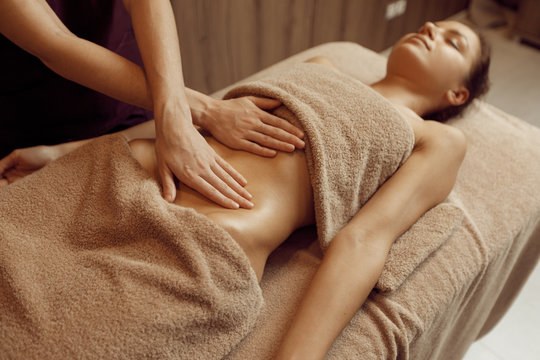 Female masseur pampering stomach to young woman