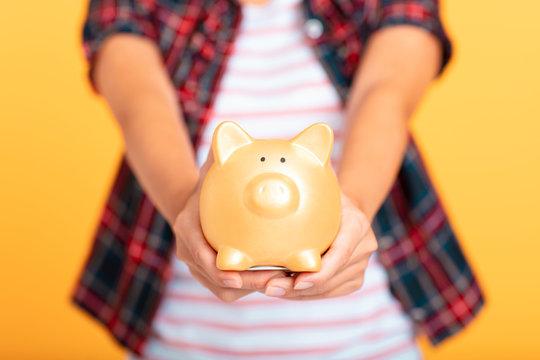 young asian woman  showing piggy bank