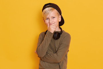 Horizontal shot of happy blond little boy poses isolated over yellow background, wearing black backwards cap, green shirt, holding headphones around his neck, keeps hands on mouth and smiling.