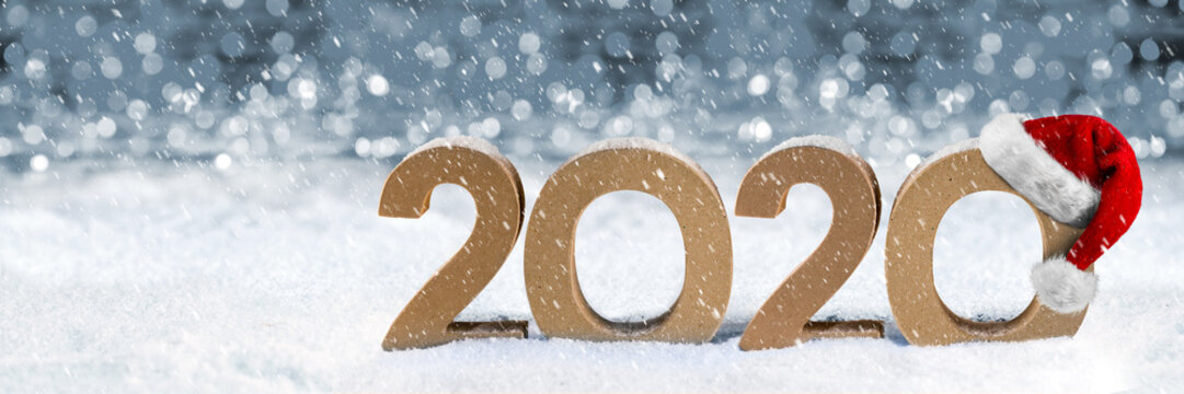 cardboard number 2020 with red white santa claus hat in snow front of bright silver bokeh wooden background. Christmas and new year´s eve holiday panorama concept.