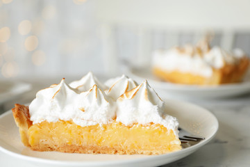Plate with piece of delicious lemon meringue pie on white marble table