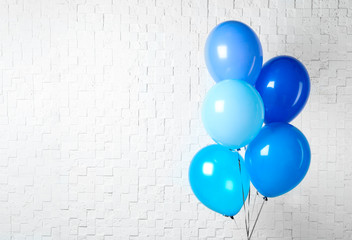 Bunch of blue balloons near white wall, space for text. Greeting card