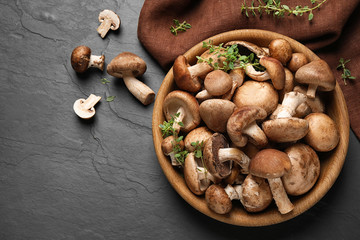 Different fresh wild mushrooms in bowl on black background, flat lay