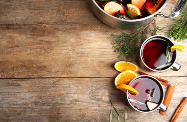 Tasty mulled wine with spices on wooden table, flat lay. Space for text