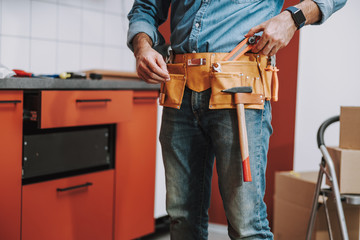 Professional repairman taking box cutter from tool belt stock photo