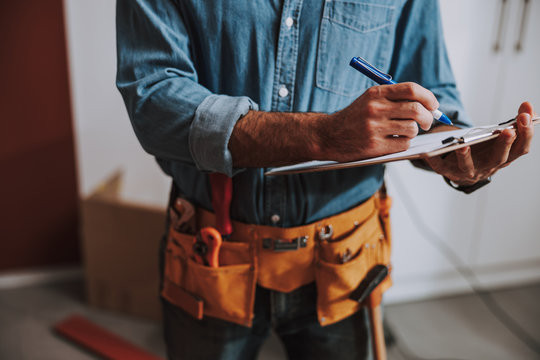 Construction worker writing on clipboard stock photo