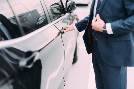Man in suit getting into car stock photo