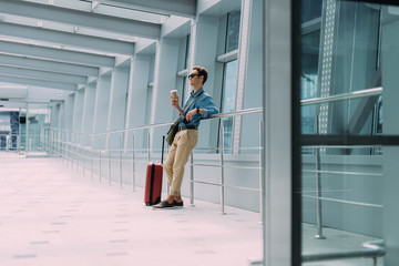 Wall Mural - Man with suitcase drinking coffee at airport stock photo