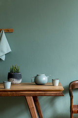 Stylish and minimalistic dining room interior with wooden table, teapot with cups, plant and elegant accessories. Eucalyptus color. Ready to use. Template. Modern home decor. Copy space.