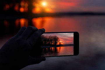 Photographing sunset on a smartphone.
