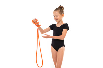 Picture of girl gymnast in black trico in full height keep a jumping-rope in her hand isolated on a white background