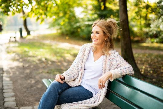 Ältere attraktive Frau sitzt lächelnd auf einer Bank