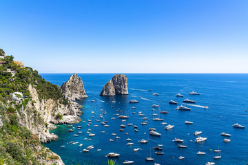 Wide panoramic view from Gardens of Augustus with the Faraglioni and blue sea full of boats and yachts, Italy