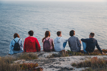 A group of young people sits with their backs together with ocean views, friendships adventure and travel. Community Values