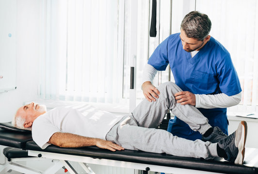physiotherapist treating leg injury on a man lying down. Senior man training with his therapist. Joint, knee and leg pain treatment