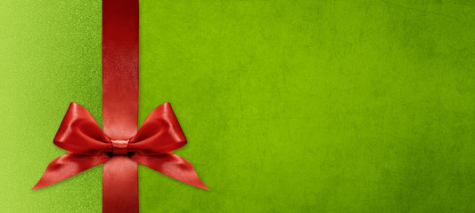 gift card wishes merry christmas background with red ribbon bow on green shiny vibrant color texture template with blank copy space