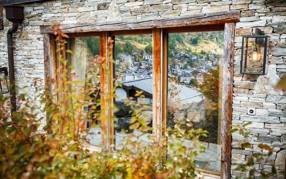 Wide window of luxury hotel with classy view on Zermatt, Swiss luxury ski resort. Autumnal scenery.