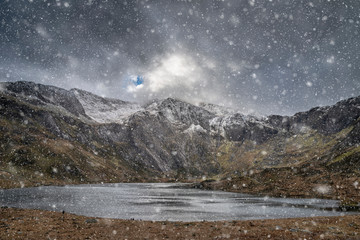 Poster Grijs Beautiful moody Winter landscape image of Llyn Idwal and snowcapped Glyders Mountain Range in Snowdonia
