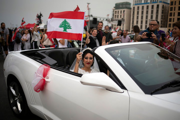 A bride waves a Lebanese flag as she and the groom drive past ongoing anti-government protests in downtown Beirut