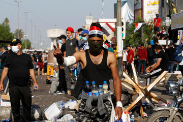 A demonstrator caries bottles of yeast, soda and water to protect himself from tear gas during a protest over corruption, lack of jobs, and poor services, in Baghdad