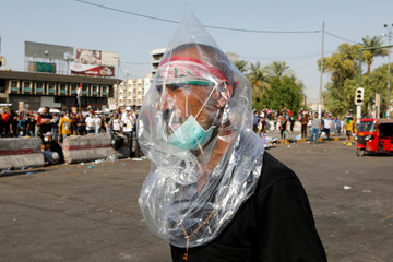 A man wears a plastic bag to protect himself from tear gas during a protest over corruption, lack of jobs, and poor services, in Baghdad