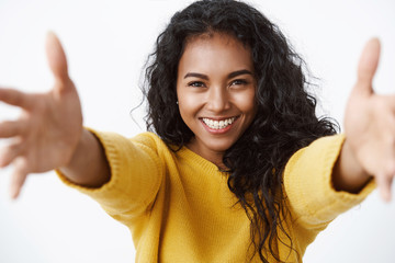 Close-up tender and cute pretty african american curly-haired woman in yellow sweater stretchin hands forward, smiling and gazing camera with love and care to give hug, cuddle friend