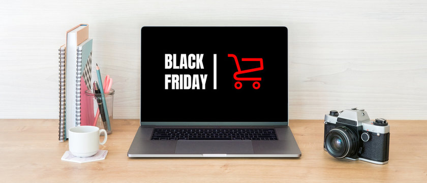 """Black Friday concept. Laptop screen with text sign """"Black Friday"""" and shopping cart on women workplace"""
