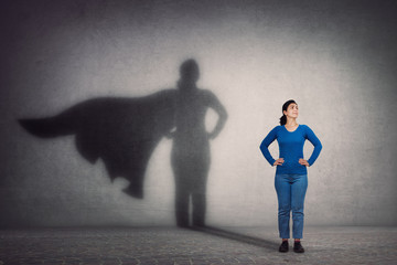 Brave woman keeps arms on hips, smiling confident, casting a superhero with cape shadow on the...