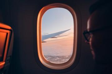 Man looking throught vindow of airplane