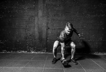 Young strong fit muscular sweaty man with big muscles strength cross workout training with dumbbells weights in the gym dark image with shadows real people black and whit