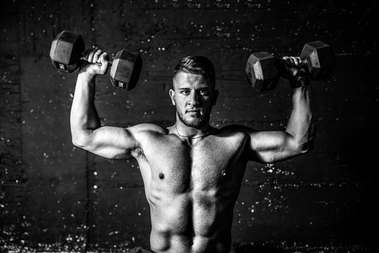 Young fit strong sweaty man shoulders workout training with two dumbbells in the gym dark image with shadows real people black and white