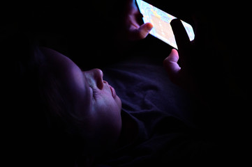 A photo of a child in an apartment sitting in front of a screen playing a game. at night. Concept new technologies, the impact of the Internet on children.