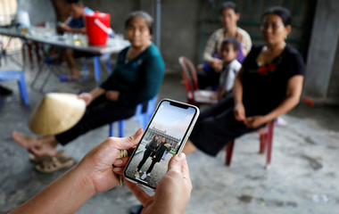 A relative shows a picture taken in Berlin of Anna Bui Thi Nhung, a Vietnamese suspected to be among dead victims found in a lorry in Britain, at her home in Nghe An province