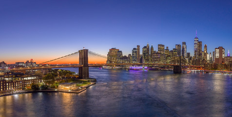 Fototapete - New York City downtown buildings skyline Brooklyn Bridge sunset evening night