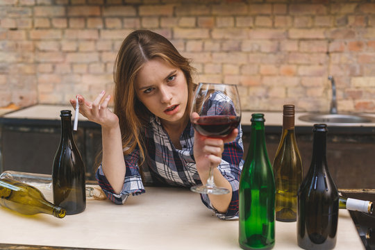 Young sad and wasted alcoholic woman sitting at kitchen couch drinking red wine and smoking, completely drunk looking depressed lonely and suffering hangover in alcoholism and alcohol abuse.