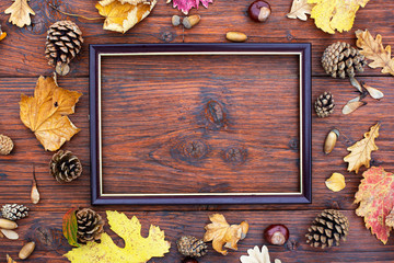 Photo frame on a wooden table with autumn leaves, pine cones and chestnuts.