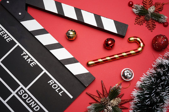 Filmmaker clapperboard with christmas decorations on red background. A Christmas movies and holiday classic cinema and TV flicks conceptual