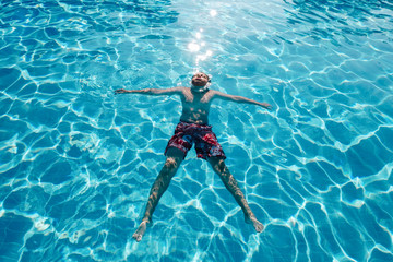 Fotobehang Ontspanning Young man floating in pool. Male in swimwear swimming in blue transparent water on sunny day. Relaxing vacation in clear sea, ocean. Summer holiday. Recreation and wellness concept
