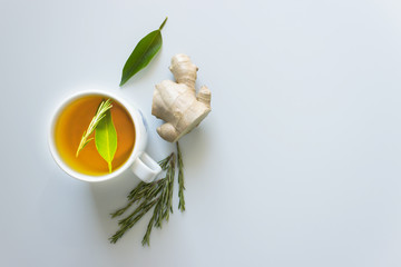 Cup of hot tea with ginger and rosemary. Concept - prevention of colds and flu, patient care. Selective focus.