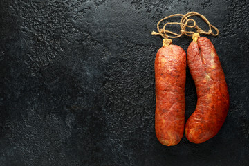 traditional Balearic raw cured meat sobrassada sausage made from ground pork, paprika and spices on rustic black background
