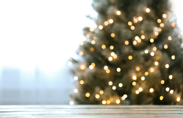 Blurred view of beautiful Christmas tree with yellow lights near window indoors, focus on wooden...