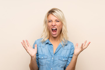 Young blonde woman over isolated background unhappy and frustrated with something