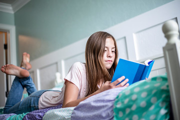 Adolescent teen girl reading a book while lying in bed at home in her bedroom. Lifestyle photo