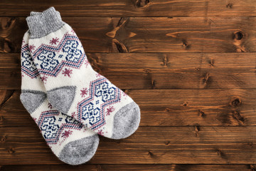 Fototapete - Knitted socks on wooden background, flat lay with space for text