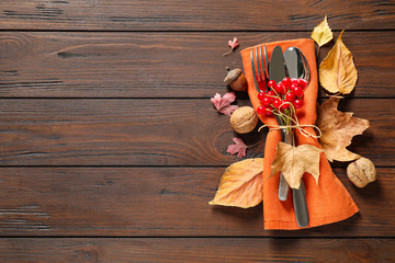Cutlery and autumn decorations on wooden background, flat lay with space for text. Happy...
